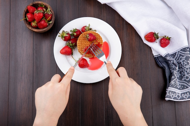 Top view of hands cutting waffle biscuit with fork and knife in plate and strawberries on cloth and in bowl on wooden surface