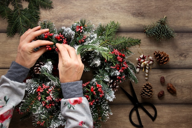 Top view hands decorating christmas wreath