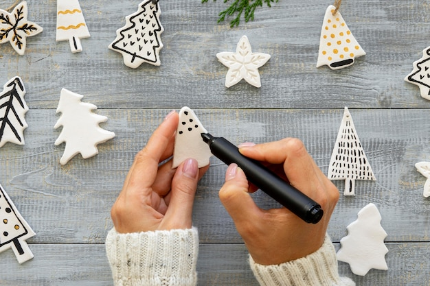 Top view of hands drawing on christmas tree decorations