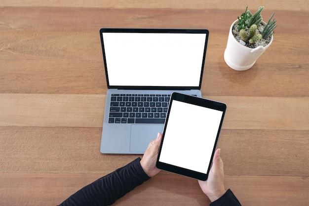 オフィスの木製のテーブルに黒いタブレットと空白の画面を持つノートパソコンを保持しているトップビュー手