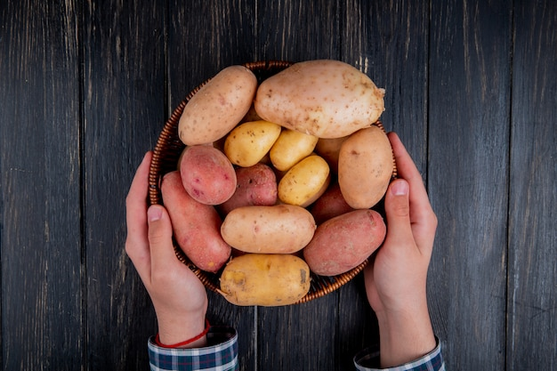 Top view of hands holding basket with potatoes on wooden surface