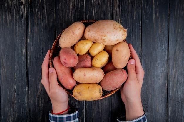 Vista superiore delle mani che tengono cestino con le patate su superficie di legno