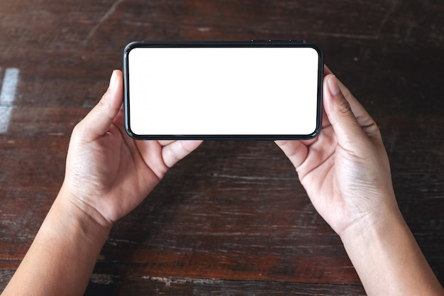 Top view  hands holding black mobile phone with blank desktop screen horizontally on wooden table background