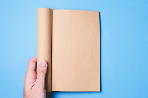 Top view of hands holding a blank book ready with copy space ready for text on blue background.