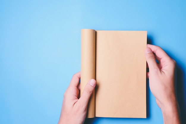 Top view of hands holding a blank book