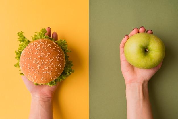 Руки взгляд сверху держа бургер и яблоко