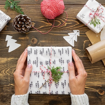 Top view of hands holding christmas gift with pine cone and string