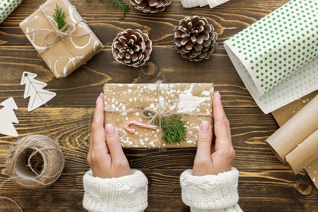 Top view of hands holding christmas gift with string and pine cones