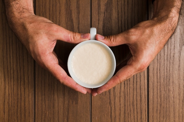 Top view hands holding cup of coffee