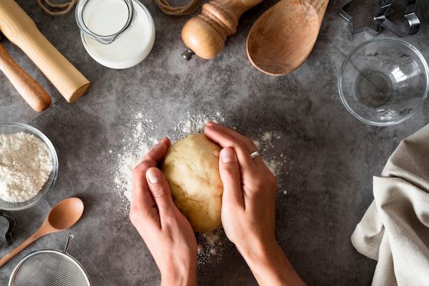 Вид сверху руки, держащие тесто на прилавке