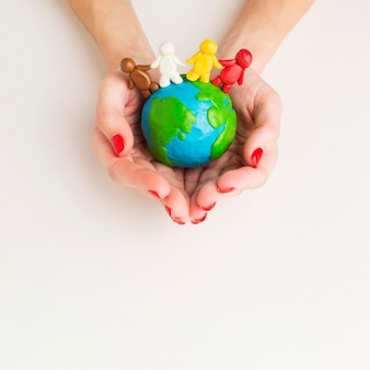 Top view of hands holding globe with people figurines
