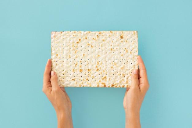 Vista dall'alto di mani che tengono il cracker ebraico