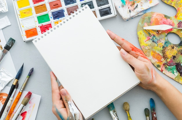 Top view hands holding notebook surrounded by painting elements