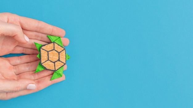 Vista dall'alto delle mani che tengono la tartaruga di carta con lo spazio della copia per il giorno degli animali