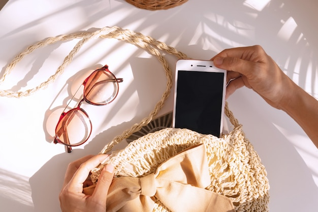 Top view of hands holding smart phone, summer bag  and sunglasses on white color background, travel concept.
