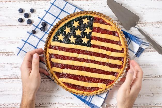 Руки взгляд сверху держа пирог флага сша