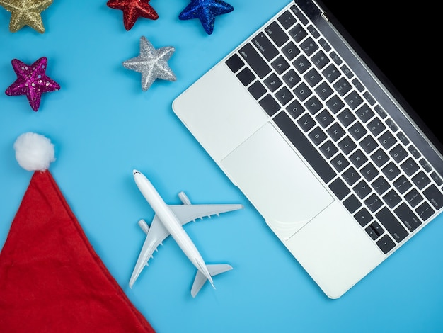 Top view of hands on laptop , smartphone , santa hat, credit card, plane and christmas orn