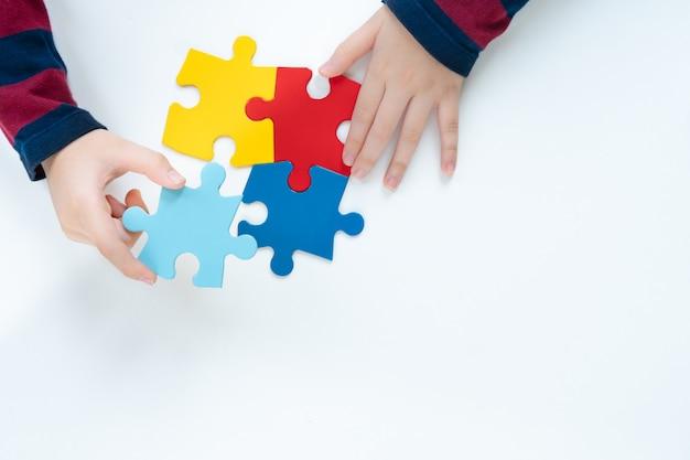 자폐증 스펙트럼 장애에 대한 대중의 인식의 컬러 퍼즐 상징을 준비하는 작은 아이의 상위 뷰 손. 세계 자폐증 인식의 날, 배려, 이야기, 캠페인, 공생. 외딴.