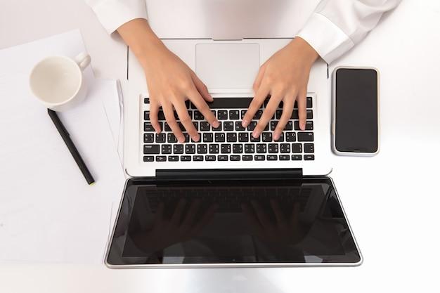 Вид сверху руки деловой женщины, работающие на современном ноутбуке. рабочий стол офиса на белом фоне.