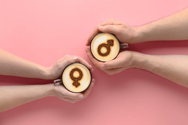 파스텔 핑크 배경에 우유 거품에 금성과 화성의 상징으로 커피 잔을 들고 사랑에 한 쌍의 상위 뷰 손. 발렌타인 데이에 개념 낭만적 인 날짜입니다. 크리 에이 티브 플랫 누워, 복사 공간