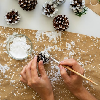 Top view of hands painting pine cones for christmas