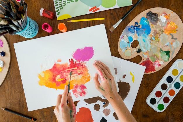 Vista dall'alto di mani che dipingono con pennelli e acquerelli