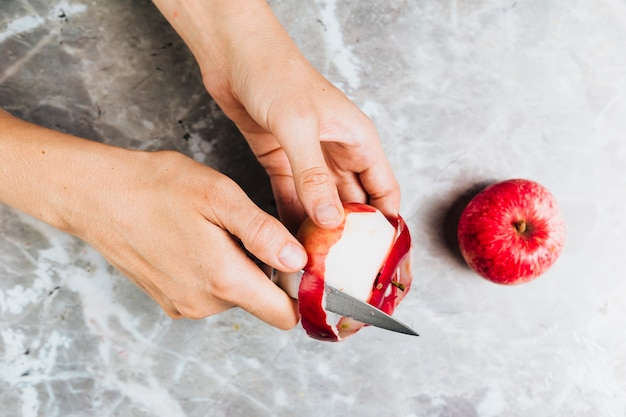Top view of hands peeling an apple on marble background