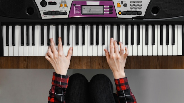 Вид сверху руки, играющие на цифровом пианино
