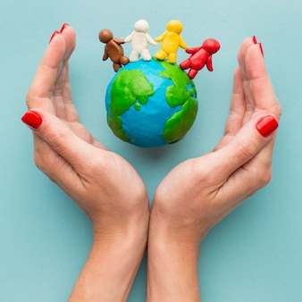 Top view of hands protecting plasticine earth and people
