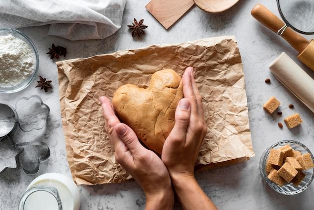 Вид сверху руки, формирующие тесто в сердце