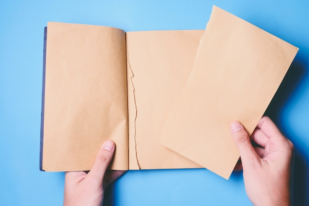 Top view of hands tear paper in notebook on blue background.