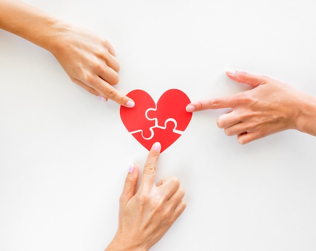Top view of hands touching puzzle heart pieces