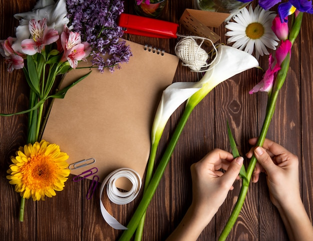 Top view of hands with gladiolus flower and pink alstroemeria with lilac daisy flowers and a sketchbook with red stapler and paper clips on wooden background