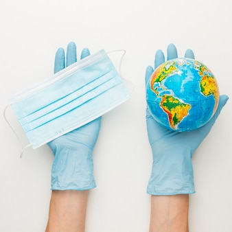 Top view of hands with gloves holding earth globe and medical mask