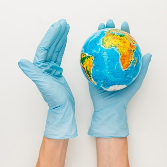 Top view of hands with gloves holding earth globe