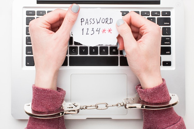 Vista superiore delle mani con le manette che tengono la password del computer portatile