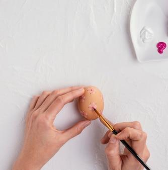 Vista dall'alto delle mani con il pennello che dipinge le uova di pasqua