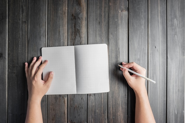 Top view of hands with pencil and open notebook