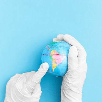 Top view of hands with surgical gloves holding earth globe