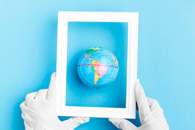 Top view of hands with surgical gloves holding frame over earth globe
