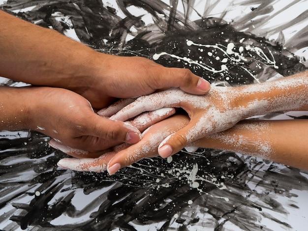 Vista dall'alto di mani con vernice bianca