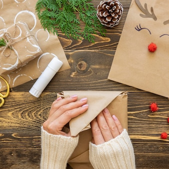 Top view of hands wrapping christmas gift paper