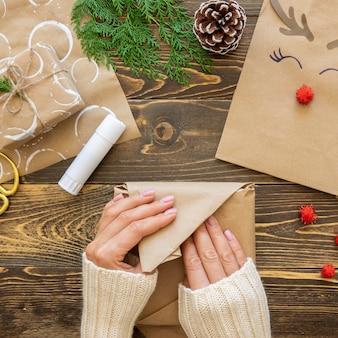 Vista dall'alto delle mani che avvolgono la carta regalo di natale