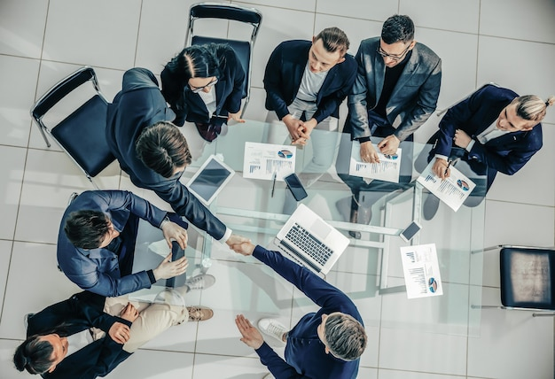 Top view handshake of happy employees at a work meeting