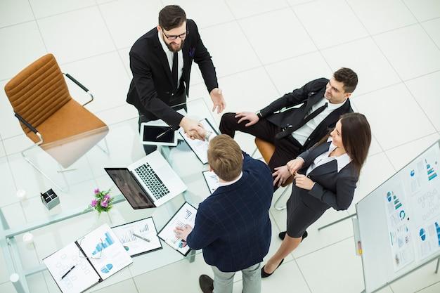 Вид сверху - рукопожатие деловых партнеров перед презентацией нового проекта в современном офисе
