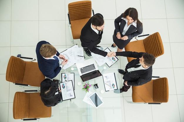 Вид сверху - рукопожатие деловых партнеров перед переговорами у рабочего стола в современном офисе. фотография - это пустое место для вашего текста