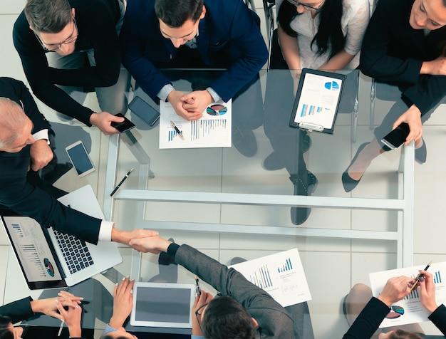 上面図。仕事の会議でのビジネスマンの握手。協力の概念