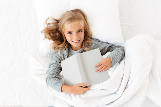 Top view of happy blonde girl lying in bed with gray book,