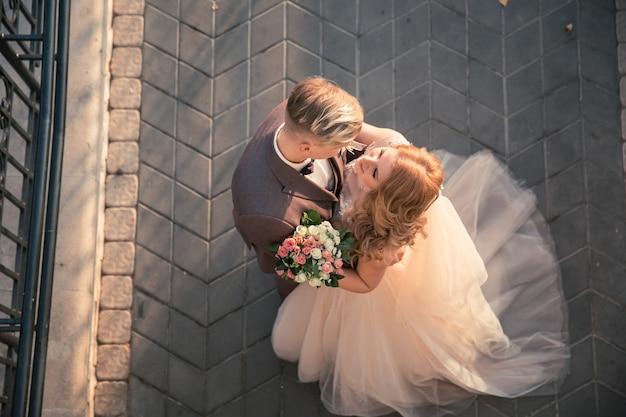 Вид сверху. счастливая невеста и жених, стоя на каменной мостовой. фото с копией пространства
