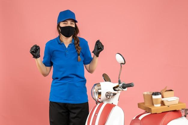 Vista dall'alto della ragazza del corriere felice che indossa guanti con maschera medica in piedi accanto alla moto con una torta di caffè su di esso su sfondo color pesca pastello pastel